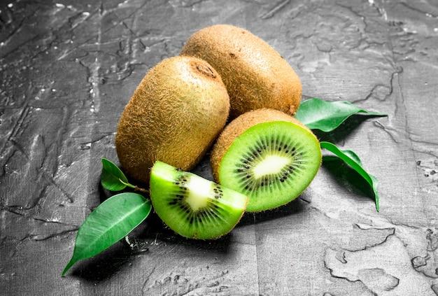 Verse kiwi met bladeren. op zwarte rustieke achtergrond