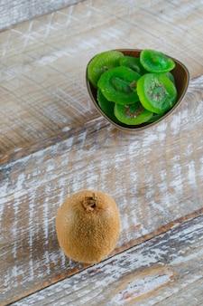Verse kiwi met gedroogde plakjes op houten tafel, hoge hoek bekeken.