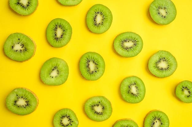 Verse kiwiplakken geïsoleerd op gele achtergrond, bovenaanzicht. biologische vegetarische voeding, kruideniersassortiment, natuurlijke ecoproducten, gezond levensstijlconcept