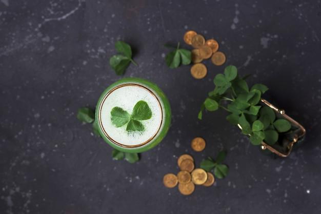 Verse klaverbladeren van een groene tas en gouden munten zijn verspreid op een donkere achtergrond. st. patrick's day concept, plat lag