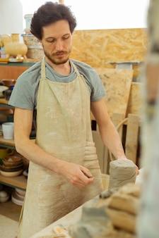 Verse klei. geconcentreerde donkerharige man in speciaal schort die de benodigde hoeveelheid klei met draad meet measuring