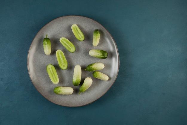 Verse kleine komkommers van ongebruikelijke kleur op een grijze plaat. bovenaanzicht. kopieer ruimte.