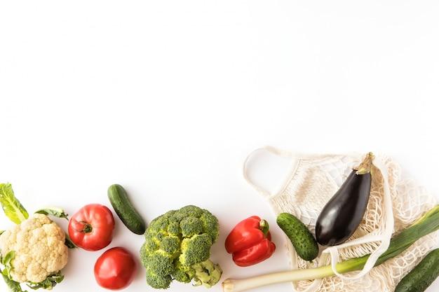 Verse kleurrijke biologische groenten en mesh katoen eco tas op witte achtergrond