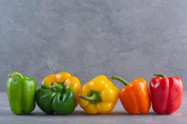 Verse kleurrijke biologische paprika's die op stenen oppervlak worden geplaatst