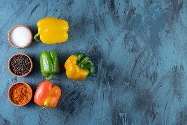 Verse kleurrijke biologische paprika's en specerijen op blauwe achtergrond.