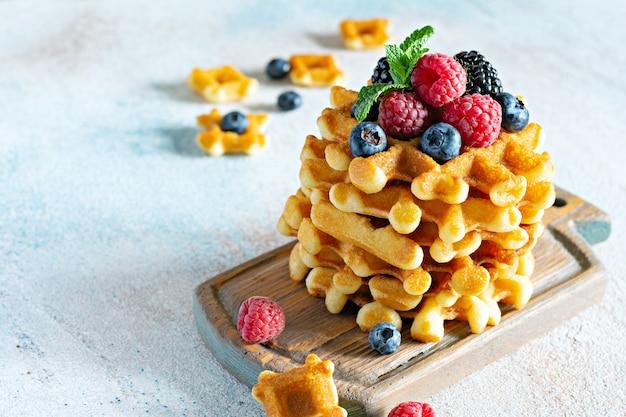 Verse knapperige belgische wafels voor het ontbijt met rijpe bessen (frambozen, bosbessen, bramen), munt en poedersuiker op een houten bord op een lichte achtergrond.