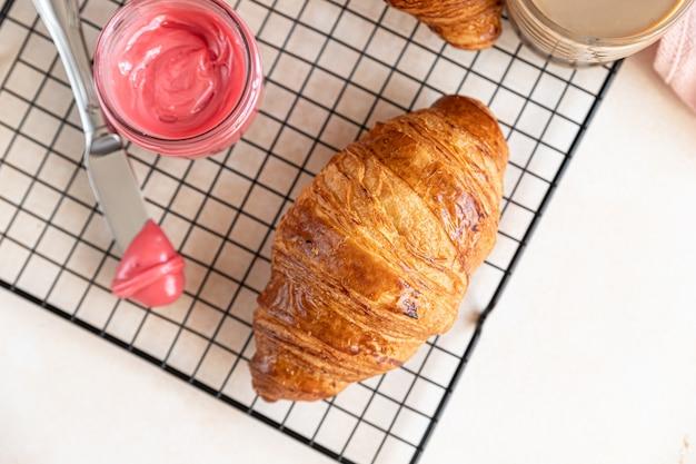 Verse knapperige croissants met roze honing op zwart metalen rooster