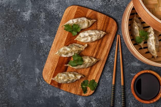 Verse knoedels op een donkere stenen ondergrond aziatische keuken, bovenaanzicht, kopie ruimte.