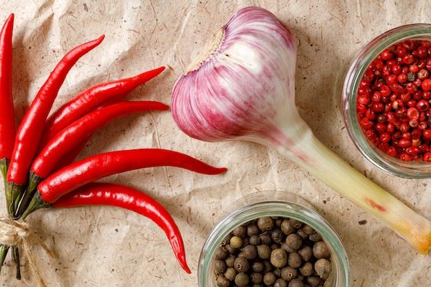 Verse knoflook, rode hete pepers, zwarte peper en braziliaanse peper op ambachtelijk papier