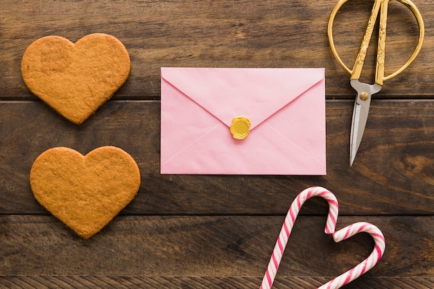 Verse koekjes dichtbij envelop, schaar en snoepriet