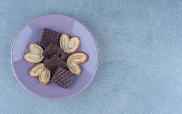 Verse koekjes en chocoladewafels op paarse plaat.