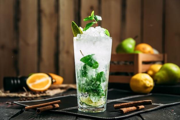 Verse koele mojitococktail in een longdrinkglas op de houten horisontal, zijaanzicht achtergrond