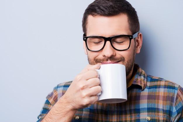 Verse koffie drinken. knappe jonge man die een kopje koffie vasthoudt en de ogen gesloten houdt terwijl hij tegen een grijze achtergrond staat