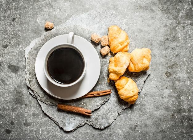 Verse koffie en croissants. op de stenen tafel.
