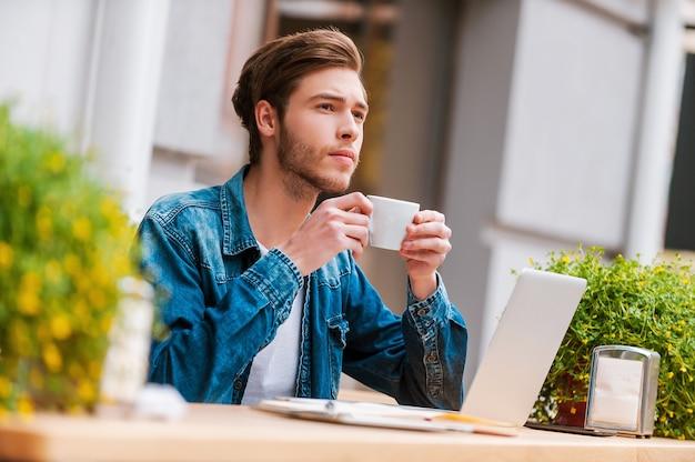 Verse koffie voor frisse ideeën. nadenkende jonge man met kopje koffie