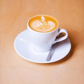 Verse koffie voor jou. bovenaanzicht van kopje verse koffie op de houten tafel