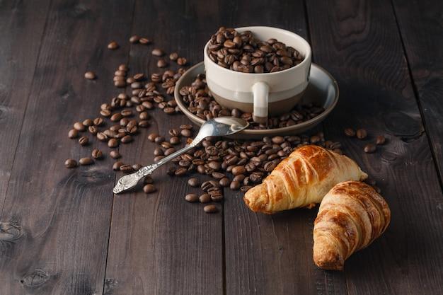 Verse koffiebonen en croissants op houten oppervlak