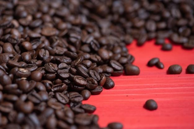 Verse koffiebonen op rode lijst. donkere vers gebrande koffiebonen achtergrond. ochtend