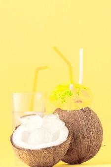 Verse kokosnootcocktail met rietjes op gele achtergrond.