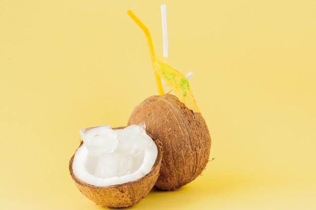 Verse kokosnotencocktail met stro op gele achtergrond, exemplaarruimte