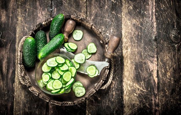 Verse komkommer op een oud dienblad. op een houten achtergrond.