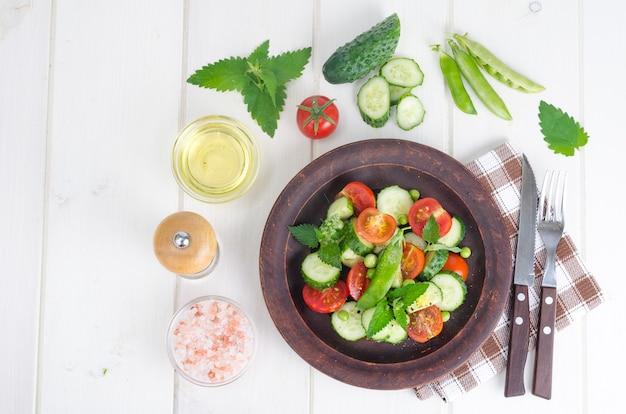 Verse komkommer, tomaat, groene erwten op keramische kom.