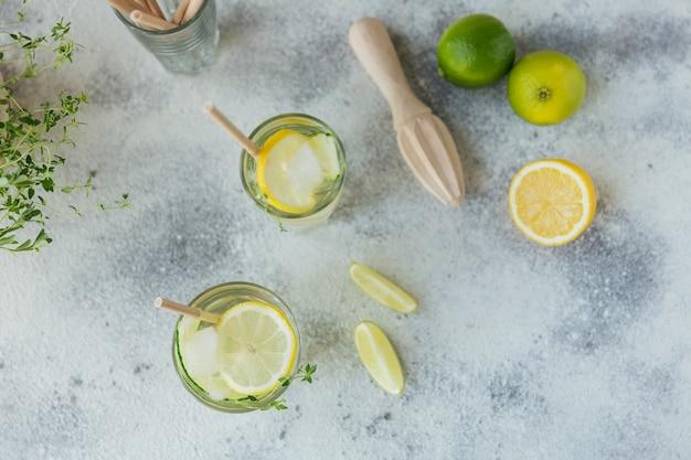 Verse komkommercocktail in een glas. zomercocktail met komkommer, limoen, tijm en ijsblokjes op houten tafel
