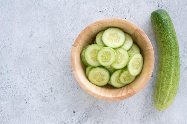 Verse komkommerplakken op een houten kom. bovenaanzicht