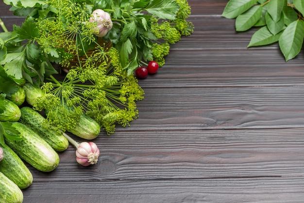 Verse komkommers, dille en kersentakjes, knoflook en kersenbessen. ruimte kopiëren. houten achtergrond. bovenaanzicht.