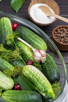 Verse komkommers, dille, knoflook en kersenbes in glazen kom. zout en piment in houten kommen. bovenaanzicht.