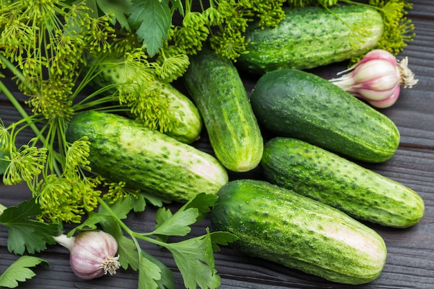 Verse komkommers. dille takjes met zaden en hoofd van knoflook. detailopname. houten achtergrond. bovenaanzicht.