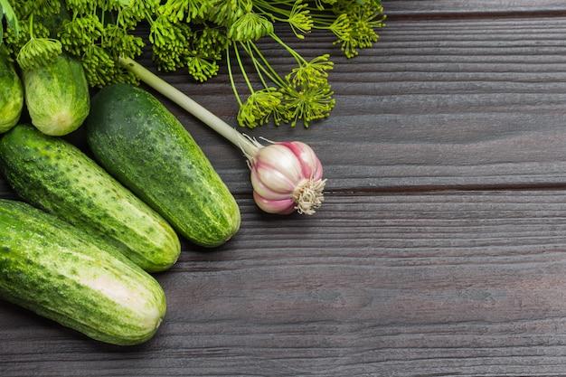 Verse komkommers. dille takjes met zaden en hoofd van knoflook. houten achtergrond. bovenaanzicht. ruimte kopiëren