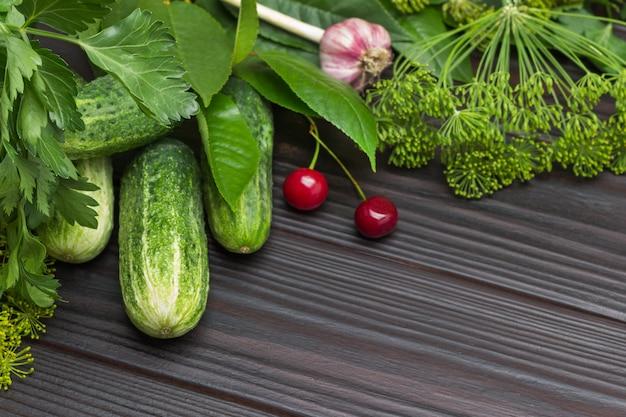 Verse komkommers en kersen onder dille en peterselie. hoofd van knoflook. houten achtergrond. bovenaanzicht. ruimte kopiëren