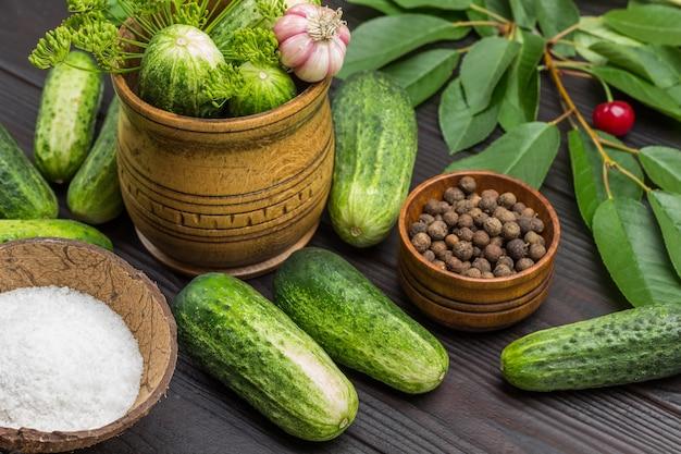 Verse komkommers en kersentakjes onder dille en peterselie. hoofd van knoflook. zout en piment in houten kommen. thuis gefermenteerde groenten. houten achtergrond. bovenaanzicht.