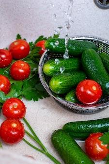 Verse komkommers en tomaten in een gootsteen
