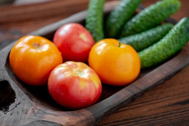 Verse komkommers en tomaten op een houten ondergrond.