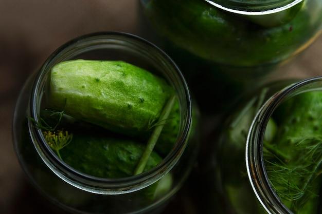 Verse komkommers in beitspotten. traditionele russische snacks. bovenaanzicht. detailopname.