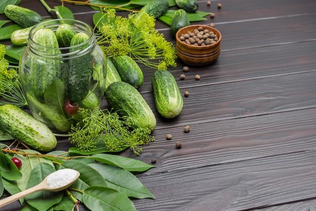 Verse komkommers in glazen pot. komkommers, dille en kersentakje op tafel. zout in houten lepel. ruimte kopiëren. houten achtergrond. bovenaanzicht.