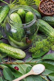 Verse komkommers in glazen pot. komkommers, dille en kersentakje op tafel. zout in houten lepel. zelfgemaakte fermentatieproducten. houten achtergrond. bovenaanzicht.