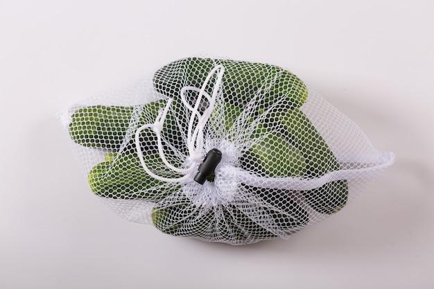 Verse komkommers in herbruikbaar verpakkingsnet dat op witte achtergrond wordt geïsoleerd