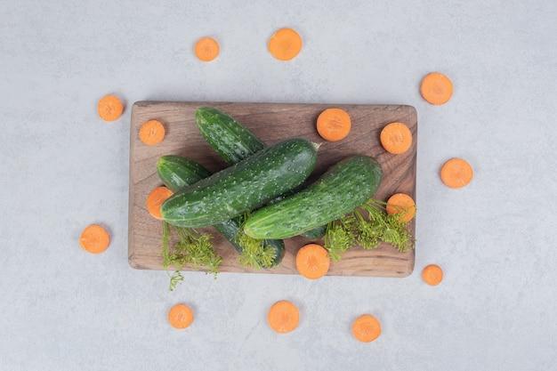 Verse komkommers met plakjes wortel op een houten bord. hoge kwaliteit foto