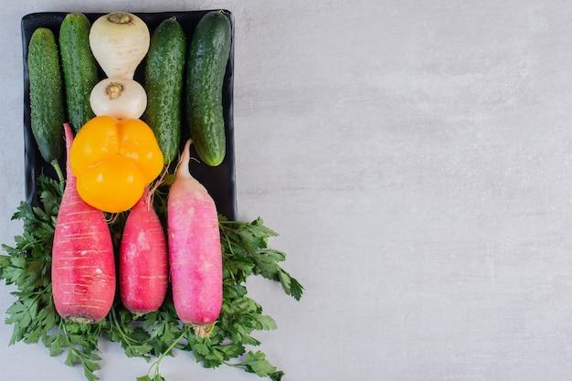Verse komkommers, rode radijs en peper op zwarte plaat. hoge kwaliteit foto