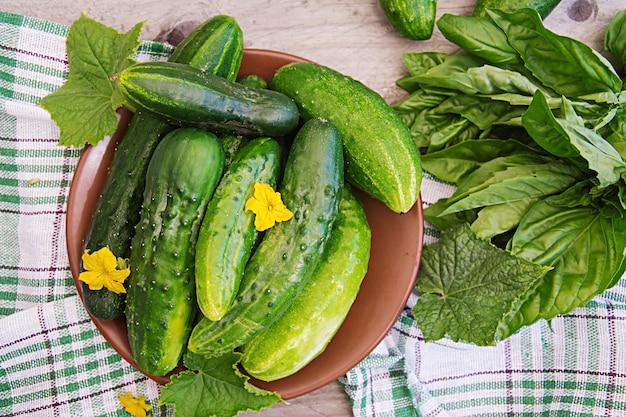 Verse komkommers uit de tuin op de tafel in de zomertuin. bovenaanzicht