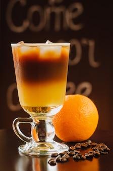 Verse koude oranje cocktail met koffie op houten tafel.