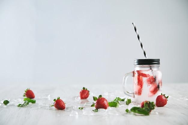 Verse koude zelfgemaakte limonade van aardbei en bruisend water in rustieke pot met streepstro op wit wordt geïsoleerd.