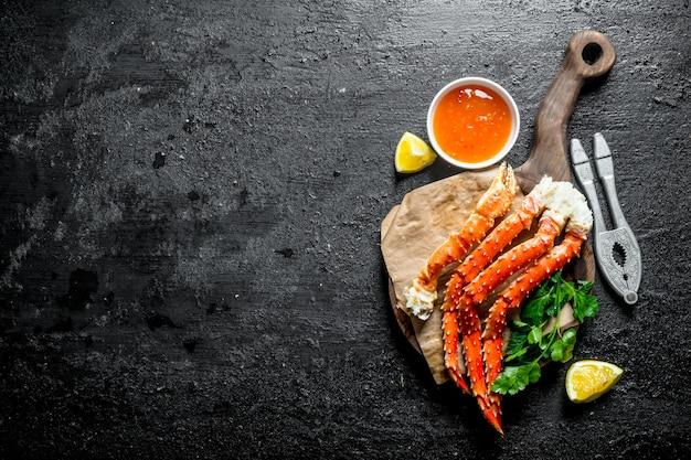 Verse krab met schijfje citroen, peterselie en saus. op zwarte rustieke tafel