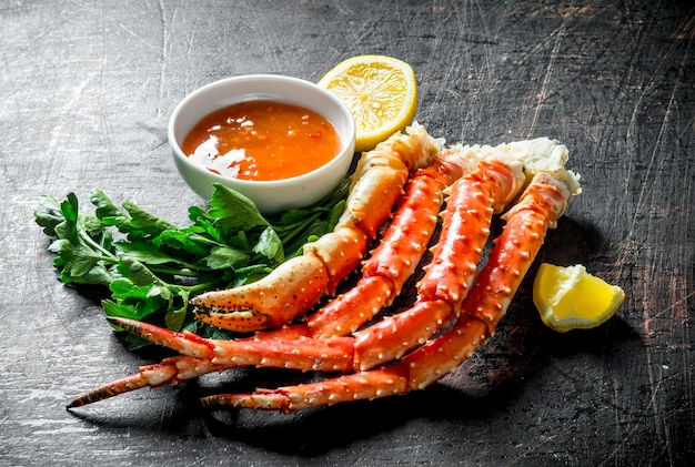 Verse krab met schijfjes citroen, peterselie en saus. op donkere rustieke achtergrond