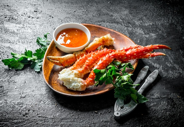 Verse krab op een bord met peterselie en saus. op zwarte rustieke tafel