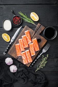 Verse krabvlees stick surimi met blauwe zwemmende krab set, op houten snijplank, op zwarte houten tafel tafel, bovenaanzicht plat lag