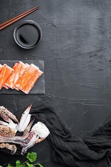 Verse krabvlees stick surimi met blauwe zwemmende krab set, op stenen bord, op zwarte achtergrond, bovenaanzicht plat lag, met copyspace en ruimte voor tekst